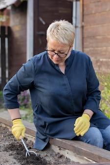 Vrouwelijke tuinman maakt vruchtbare grond los met een culti-schoffel voordat ze groenten plant