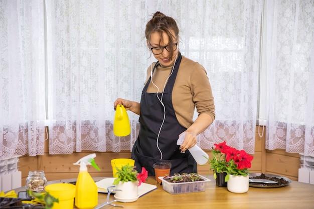 Vrouwelijke tuinman met oortelefoons met plezier in huis tuin, kamerplanten planten