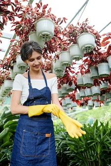 Vrouwelijke tuinman rubberen handschoenen te zetten