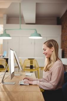 Vrouwelijke uitvoerend die aan computer in bureau werkt
