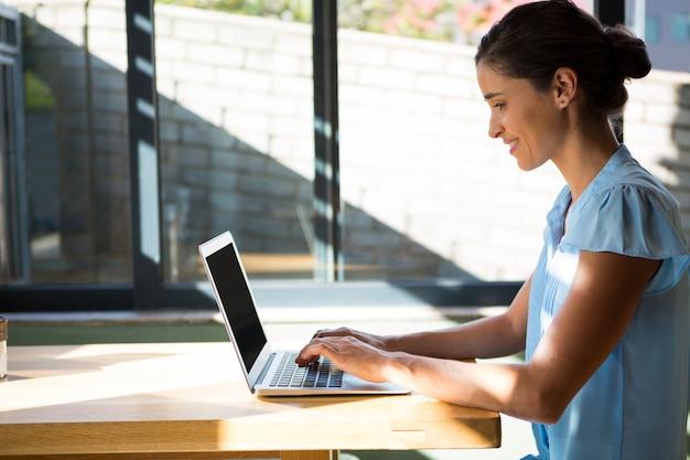 Vrouwelijke uitvoerend die aan laptop in koffie werkt