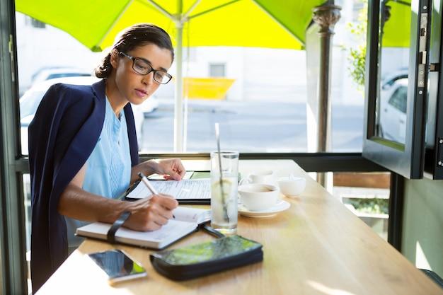 Vrouwelijke uitvoerend schrijven in dagboek in café