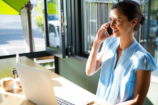 Vrouwelijke uitvoerende praten op mobiele telefoon in café