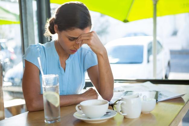Vrouwelijke uitvoerende zit in café