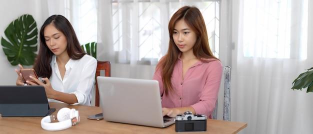 Vrouwelijke universitaire studenten die hun project met digitale apparaten en camera op houten lijst doen