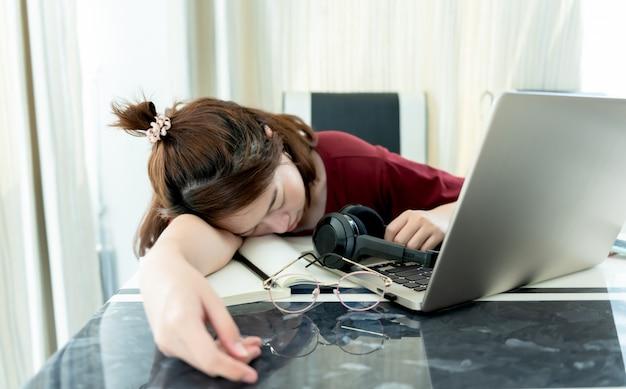 Vrouwelijke universiteitsstudent slapen op tafel wegens beproeving door thuis online te studeren