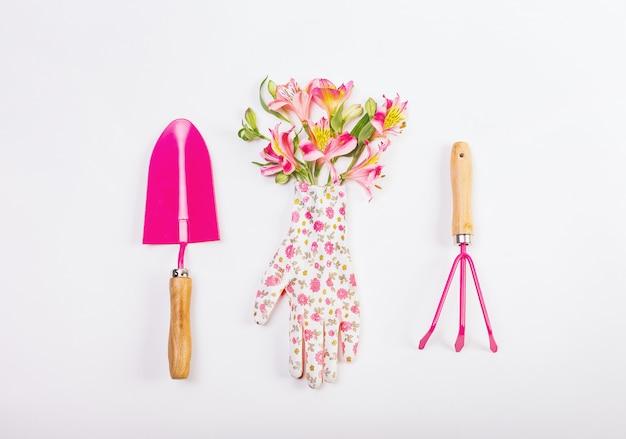 Vrouwelijke vastgestelde hulpmiddelen die tuin roze bloemen werken Premium Foto