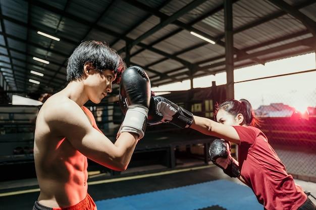 Vrouwelijke vechter aanvallen met punch beweging en mannelijke bokser doen verdediging beweging op trainingskamp