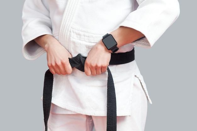 Vrouwelijke vechter torso poses in witte kimono, smartwatch en sportieve sterke armen zijn close-up zwarte band. sport en technologie gezondheidszorg concept. indoor studio-opname, geïsoleerd op een grijze achtergrond