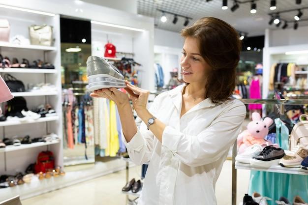 Vrouwelijke verkoopassistent in winkelcentrum toont zool van sportschoenen