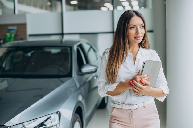 Vrouwelijke verkoper bij een autoshowroom