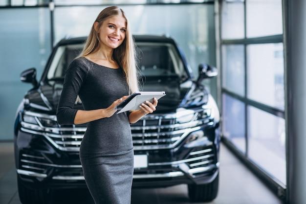 Vrouwelijke verkoper bij een autotoonzaal door de auto