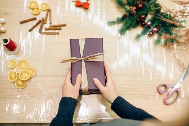 Vrouwelijke verkoper handen inwikkeling geschenkdoos