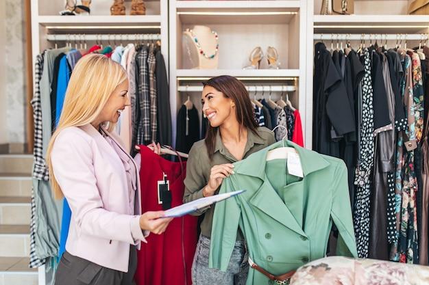 Vrouwelijke verkoper helpt koper om te kiezen tussen verschillende kleding.