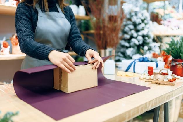Vrouwelijke verkoper houdt onverpakt kartonnen geschenkdoos