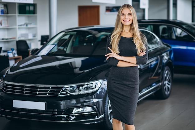 Vrouwelijke verkoper in een autotoonzaal door de auto