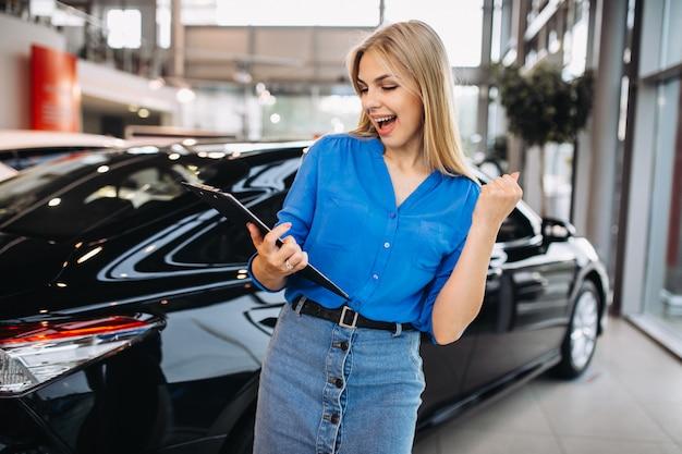 Vrouwelijke verkoper in een autotoonzaal