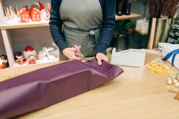 Vrouwelijke verkoper snijdt het inpakpapier met een schaar, decoratie van de geschenkdoos.