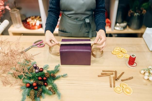 Vrouwelijke verkoper versiert geschenkdoos met inpakpapier en gouden lint, decoratieproces. vrouw wraps aanwezig op tafel, decorprocedure
