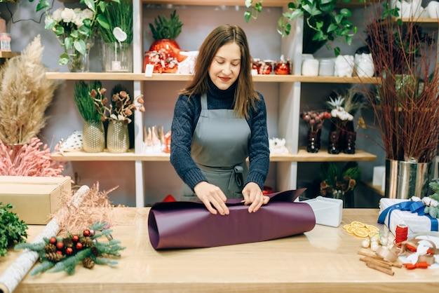 Vrouwelijke verkoper wikkelt geschenkdoos in feestelijk papier