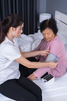 Vrouwelijke verpleegster die bloeddruk van een hogere vrouw controleert