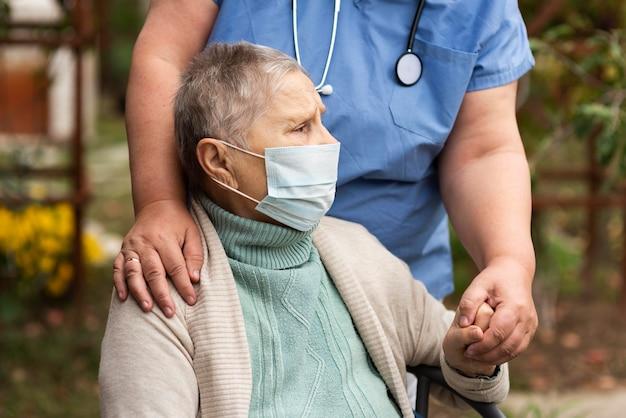Vrouwelijke verpleegster die de hand van de oudere vrouw houdt