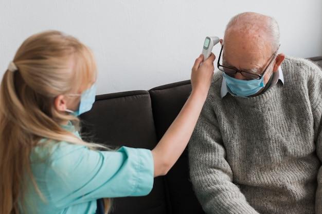 Vrouwelijke verpleegster die de temperatuur van de oude man controleert