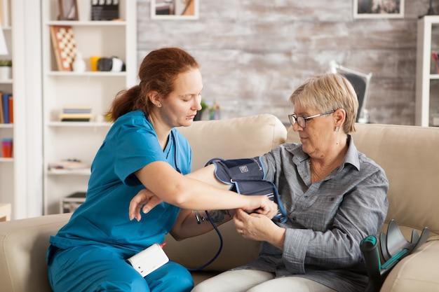 Vrouwelijke verpleegster die digitaal bloeddrukapparaat gebruikt op hogere vrouw in verpleeghuis.