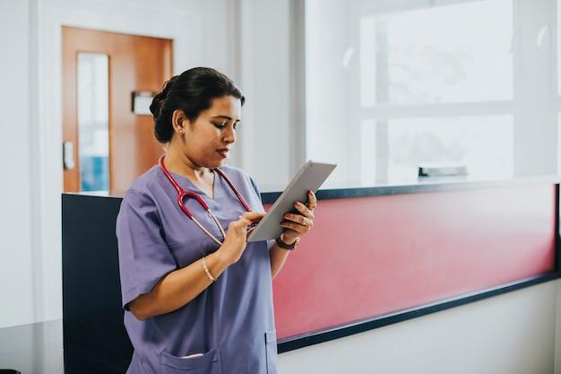 Vrouwelijke verpleegster die het schema op een tablet controleert