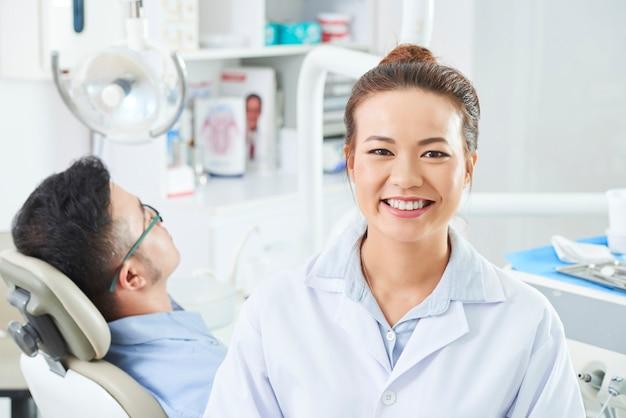 Vrouwelijke verpleegster die in tandkliniek werkt