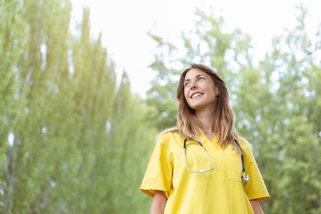 Vrouwelijke verpleegster die met een stethoscoop naar de hemel kijkt