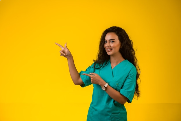 Vrouwelijke verpleegster die naar iets met de hand wijst.