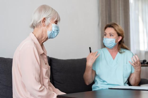 Vrouwelijke verpleegster die oudere vrouw haar controleresultaten uitlegt