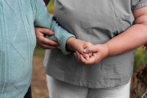 Vrouwelijke verpleegster die oudere vrouw helpt lopen