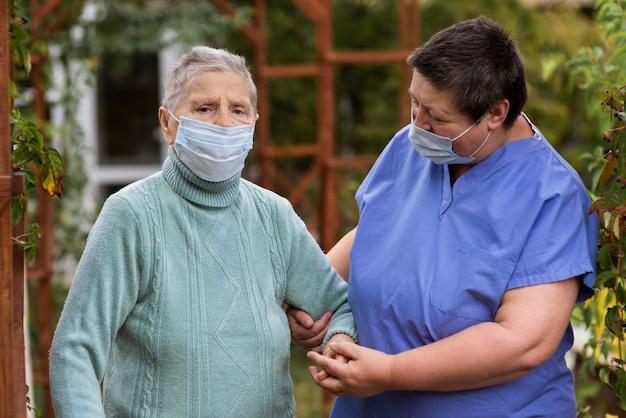 Vrouwelijke verpleegster die oudere vrouw met medisch masker behandelt