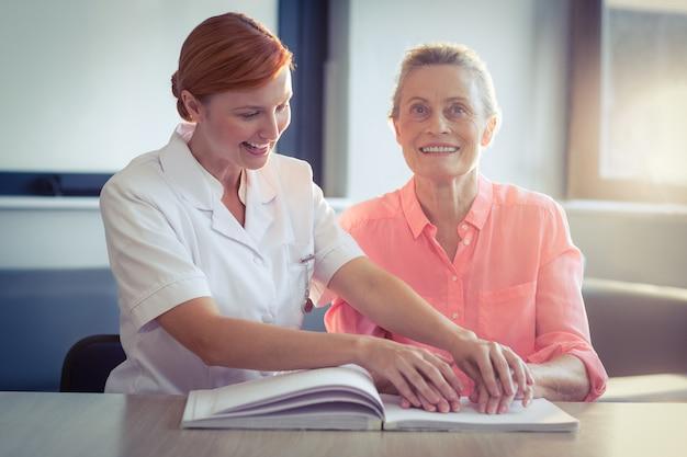 Vrouwelijke verpleegster die patiënt helpt die het braille-boek leest