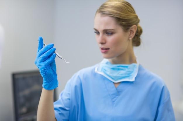 Vrouwelijke verpleegster die tandheelkundig hulpmiddel houdt