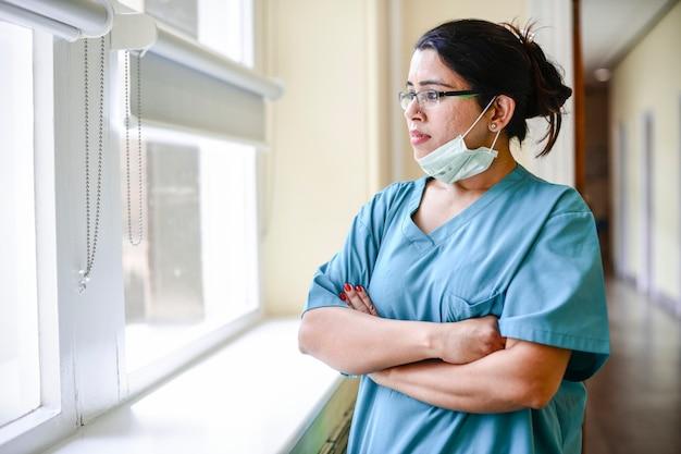 Vrouwelijke verpleegster die uit het raam staart