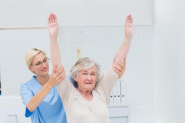 Vrouwelijke verpleegster die vrouwelijke patiënt in het uitoefenen bij kliniek helpen