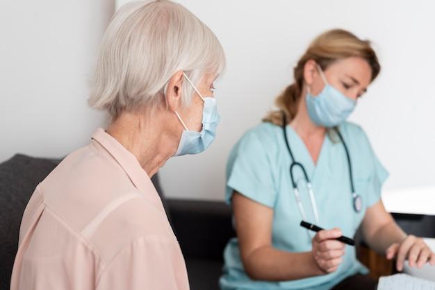 Vrouwelijke verpleegster en oudere vrouw in verpleeghuis tijdens een controle
