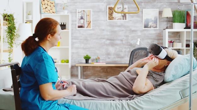Vrouwelijke verpleegster in bejaardentehuis geeft een oude gehandicapte dame een vr-headset om de pijn te verzachten en haar af te leiden terwijl ze in het ziekenhuisbed ligt