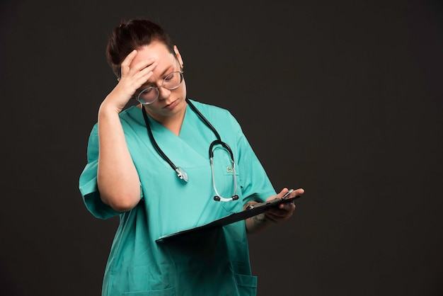Vrouwelijke verpleegster in groen uniform die de spatie houdt en denkt.