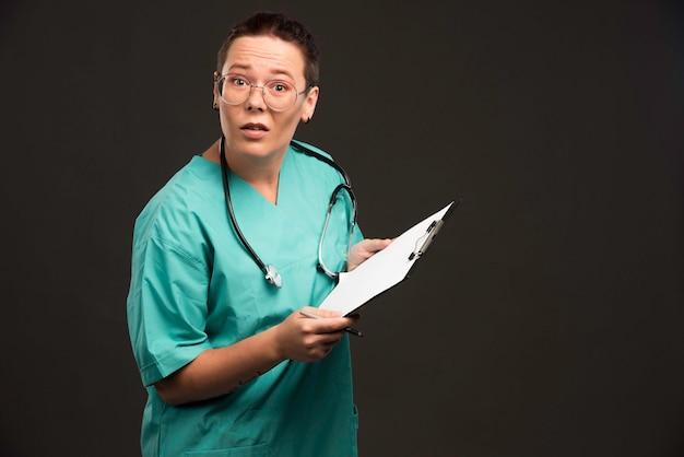 Vrouwelijke verpleegster in groen uniform die de spatie houdt en verrassend kijkt.