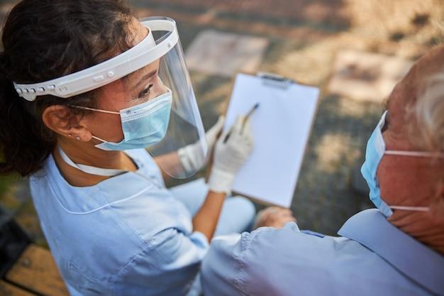 Vrouwelijke verpleegster in masker en ptotectie die naar oude patiënt kijkt