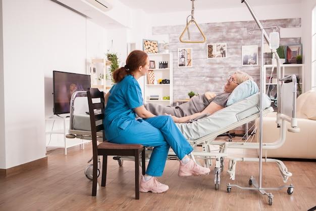 Vrouwelijke verpleegster in verpleeghuis die zieke oude vrouw controleert die in bed ligt.