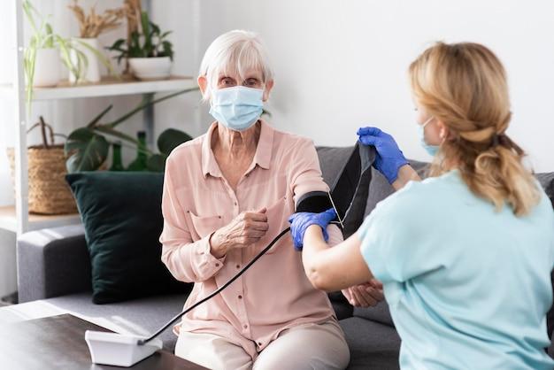 Vrouwelijke verpleegster met behulp van bloeddrukmeter op oudere vrouw