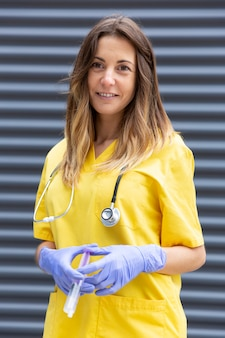 Vrouwelijke verpleegster met beschermende handschoenen en spuit in haar handen