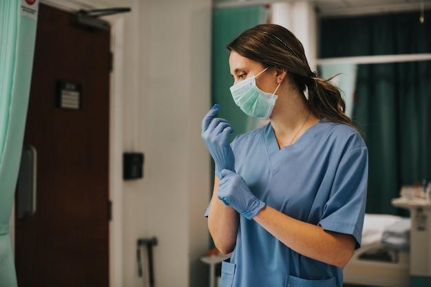 Vrouwelijke verpleegster met een masker dat handschoenen aandoet