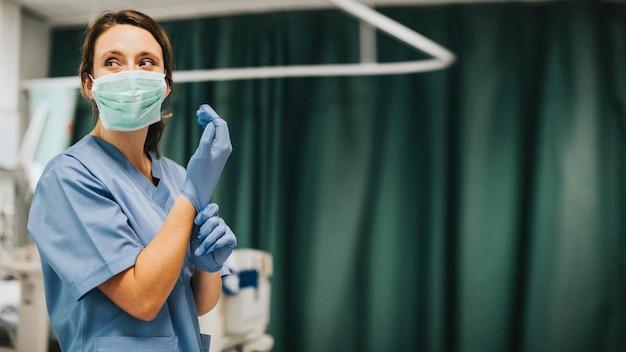 Vrouwelijke verpleegster met een masker die handschoenen aantrekt om de coronaviruspatiënt te genezen