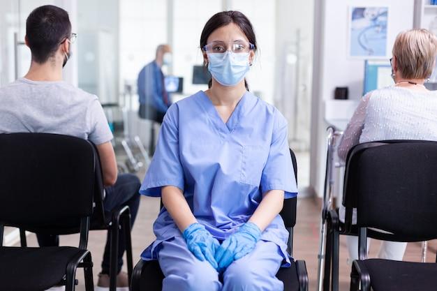 Vrouwelijke verpleegster met gezichtsmasker tegen coronavirus in wachtruimte van ziekenhuis
